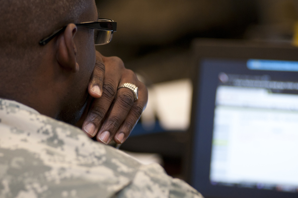 Photo over the shoulder of a soldier looking at a computer screen