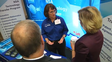 Screenshot of three people having a conversation in a presentation booth from NSA Technology Transfer video